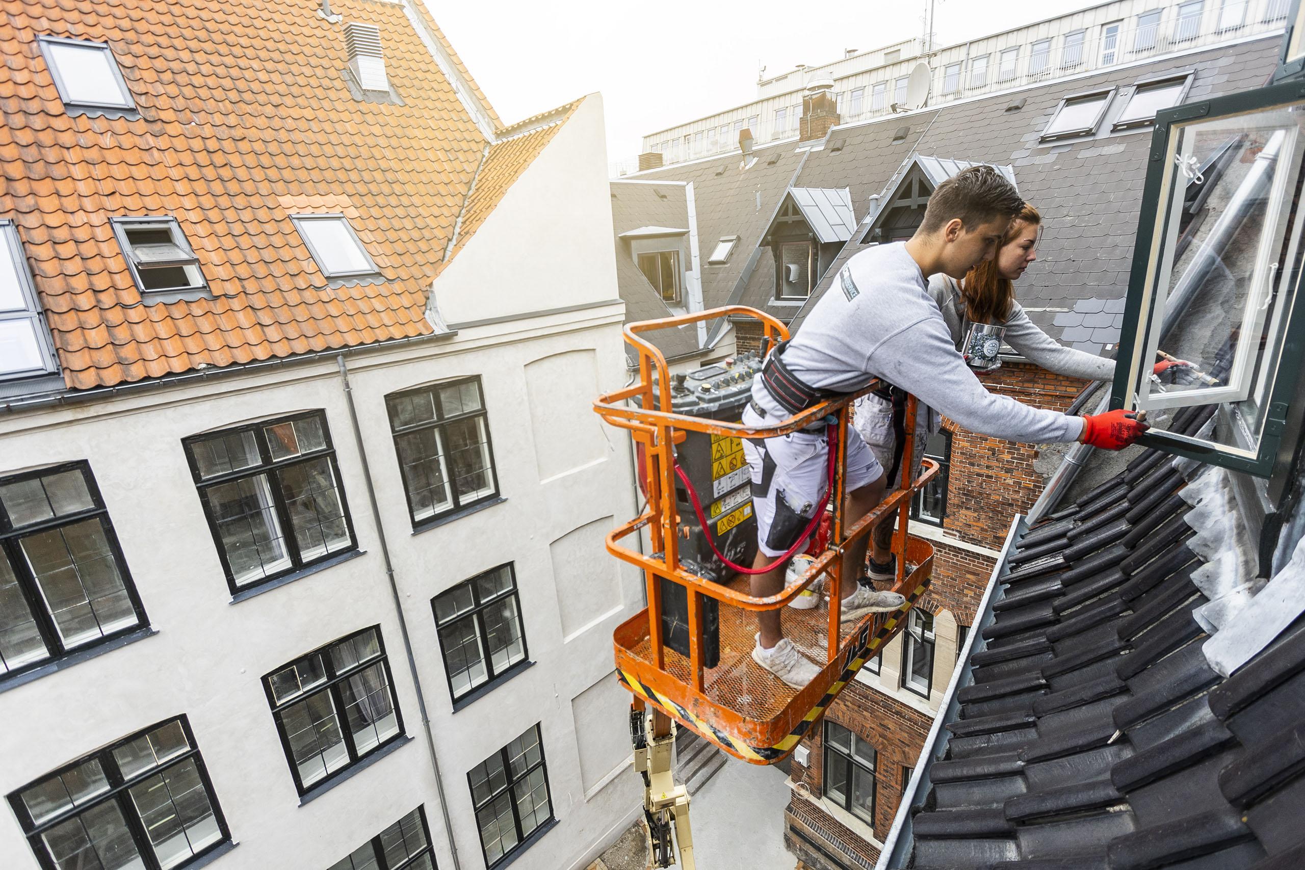 Malere står på lift og maler vindue på en lejlighed