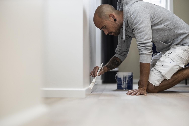 Mand maler væg hvid