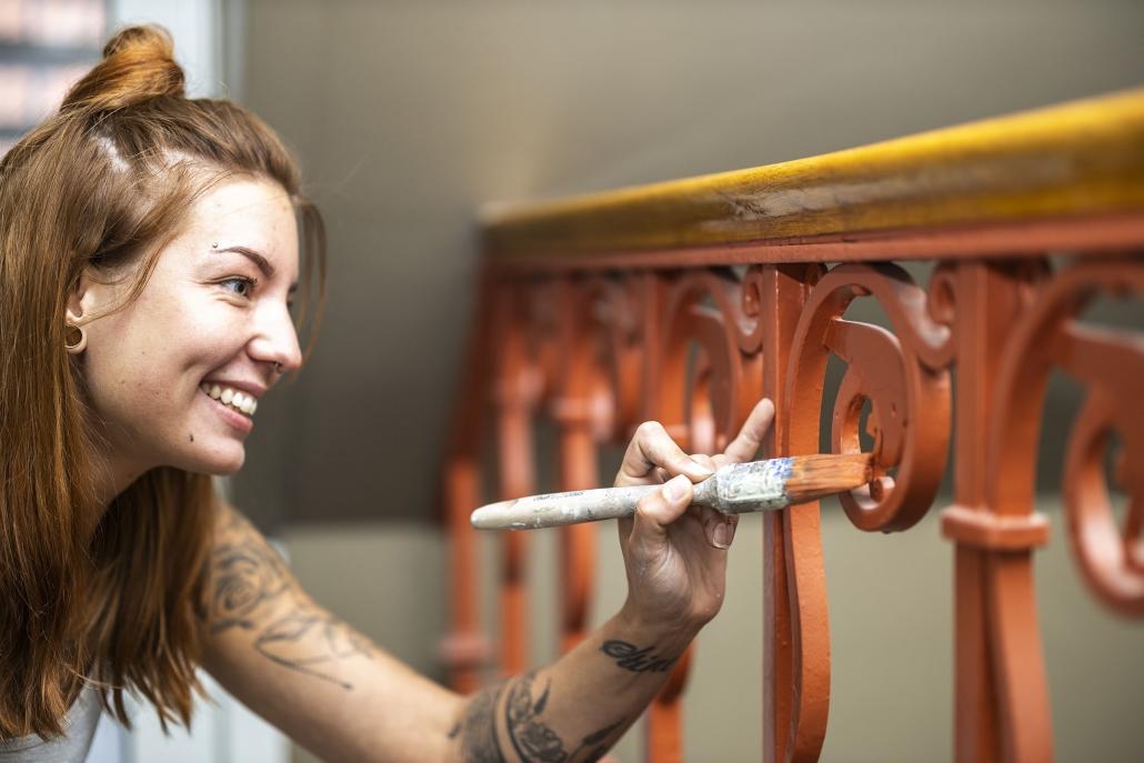 Kvinde lakerer gelænder ved trappeopgang