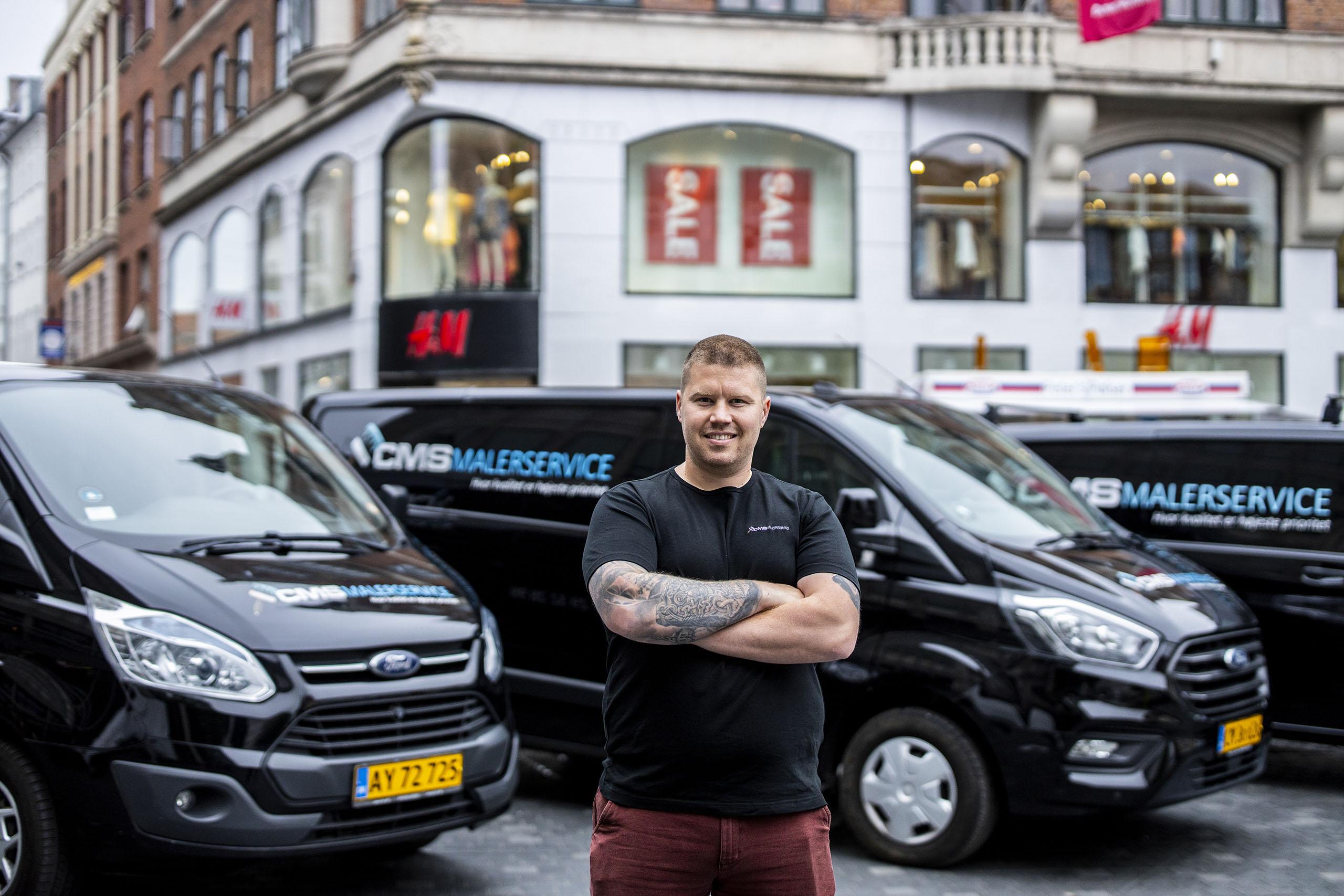 Christian poserer foran firmabilerne