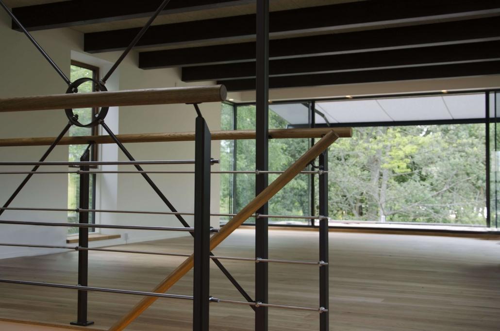 Trappe op til stue med hvidevægge og skydedør med åbnedøre ud til skov