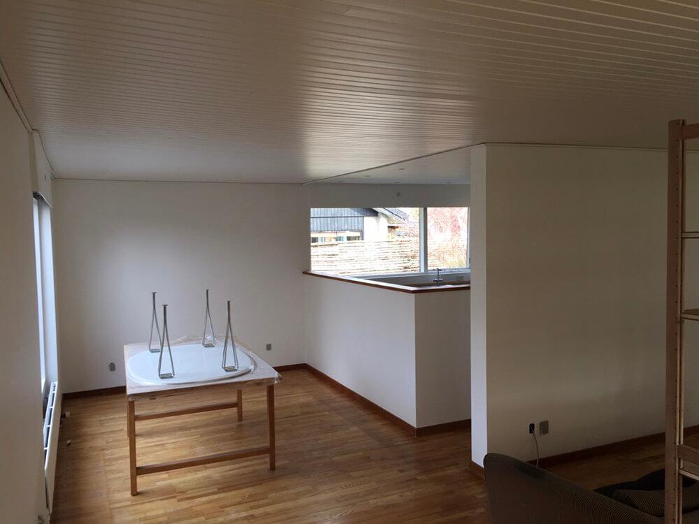 Hvidt køkkenalrum, med moderne spisebord og plankegulve